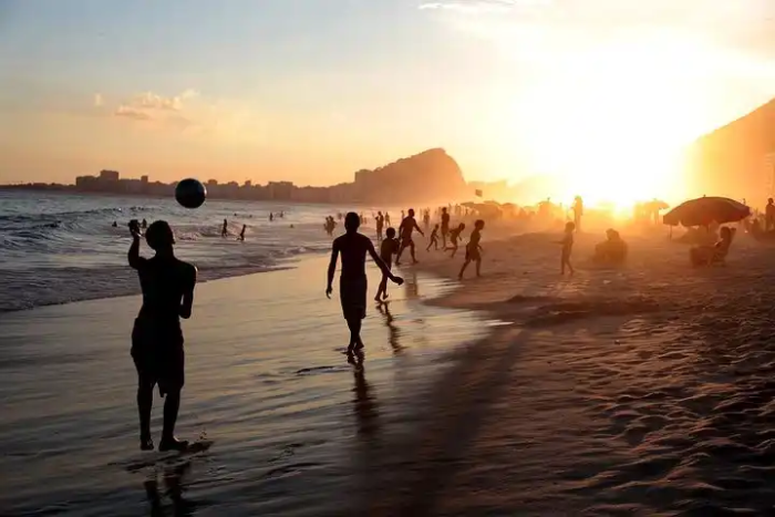 children playing soccer on the beach